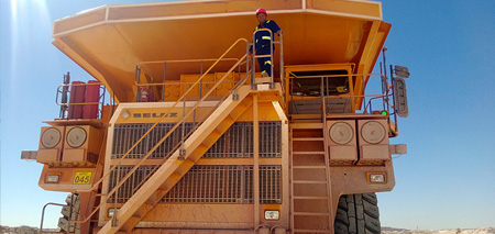 Visitors at the mine bench taking a look how BELAZ trucks are loaded